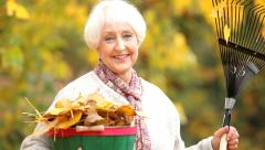 Fall portrait of senior woman with rake Stock Footage