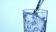 Water pouring into a glass, slow motion Stock Footage