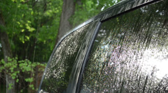 Strong rain water drops fall and splash on car roof and windows Stock Footage