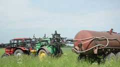 Season work equipment tractor with long sprinkler on field Stock Footage