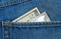 u.s. dollars and condom in the back jeans pocket - stock photo