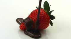 Chocolate dripping onto strawberry - stock footage