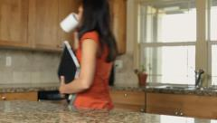 Woman in kitchen grabs things and heads to work Stock Footage