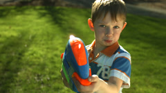 Young boy spraying squirt gun at camera - stock footage