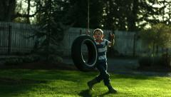 Boy playing on tire swing, slow motion Stock Footage