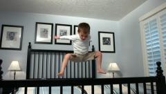 Nuori poika hyppää sänkyyn, hidastettuna Arkistovideo