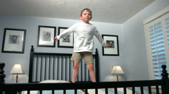 Young boy jumps on bed, slow motion Stock Footage