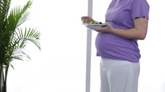 Pregnant woman eating salad - stock footage