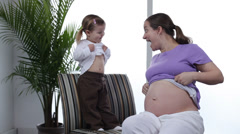 Pregnant woman and young daughter Stock Footage
