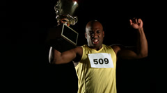Track athlete celebrating with trophy, slow motion - stock footage