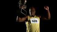 Stock Video Footage of Track athlete celebrating with trophy, slow motion