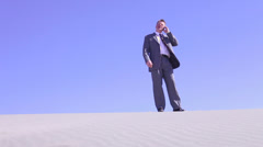 Businessman with cell phone in the desert Stock Footage