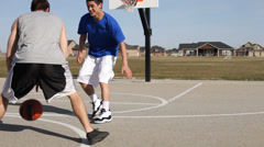 Teens play basketball Stock Footage
