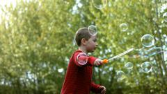 Young boy making bubbles, slow motion Stock Footage