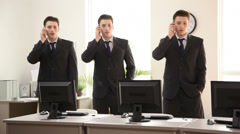 Three identical businessmen talking on phones Stock Footage