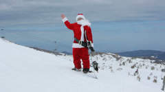 Santa Claus with snowboard waving to camera Stock Footage