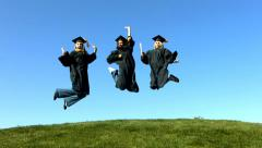 Three graduates jumping and celebrating Stock Footage