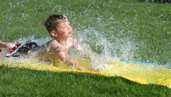 Young boy on water slide, slow motion Stock Footage