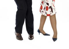Lady in colorful skirt with a partner show salsa position Stock Photos