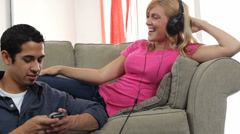 Couple at home listening to mp3 player together Stock Footage