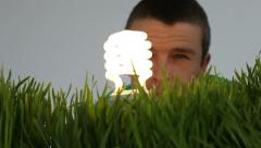 Man with light bulb and grass patch - stock footage