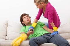 Woman disturbing her husband in watching tv Stock Photos