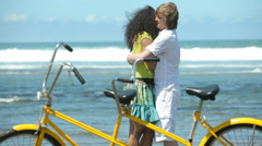 Couple at beach with tandem bicycle in foreground - stock footage