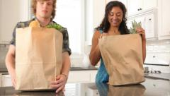 Couple in kitchen with grocery bags - stock footage