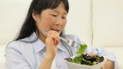 Mature Asian woman eating salad - stock footage