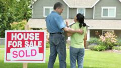 Couple look at new home, SOLD sign in foreground - stock footage