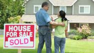 Stock Video Footage of Couple look at new home, SOLD sign in foreground