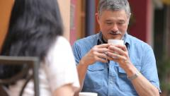 Mature Asian couple having coffee together at an outdoor cafe Stock Footage