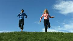 Man and woman running down grassy hill, slow motion Stock Footage