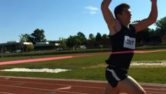 Track runner crosses finish line, slow motion Stock Footage