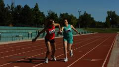 Athletes pass the baton in a track relay - stock footage