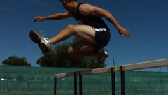 Track athlete jumps over hurdle, slow motion - stock footage