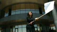 Businesswoman in front of office building waving white flag Stock Footage