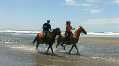 Couple horseback riding on beach, slow motion Stock Footage