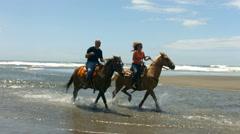 Couple horseback riding on beach, slow motion - stock footage