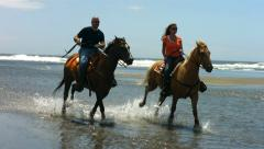 Couple riding horses on beach, slow motion - stock footage