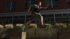 Free runner leaps across concrete blocks, slow motion Stock Footage
