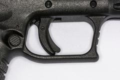 Trigger of hand gun on white background Stock Photos