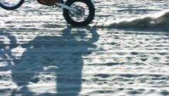 Shadow of motorcycle riding across sand, slow motion Stock Footage