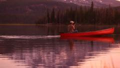 Man paddling canoe on lake at sunset - stock footage