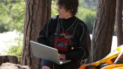 Kayaker sitting down using laptop outdoors Stock Footage
