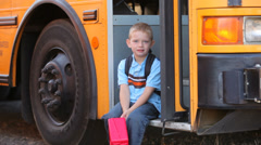 Young boy walks to front of school bus Stock Footage