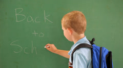 Boy writes BACK TO SCHOOL on chalk board Stock Footage
