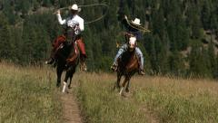 Two cowboys riding horseback swinging lassos, slow moiton - stock footage