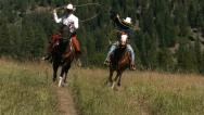 Stock Video Footage of Two cowboys riding horseback swinging lassos, slow moiton