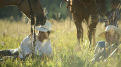 Cowboys sit in grass taking break - stock footage
